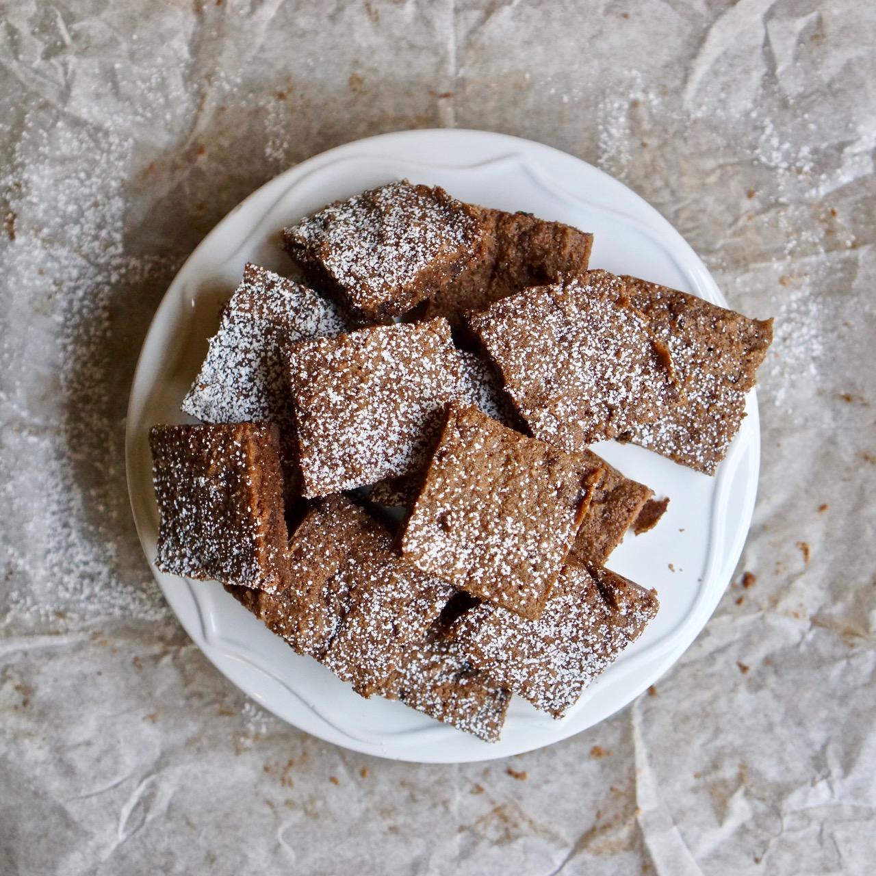 ריבועי שוקולד צ׳יפס מוכנים עם אבקת סוכר מעל מונחים על צלחת לבנה. מתוך מתכון חיתוכיות שוקולד צ׳יפס ללא קמח בלוג גבישס.