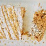 עוגת אגוזים עם אבקת סוכר מעל וזיגוג קפה. מעל פזורים אגוזים קצוצים.