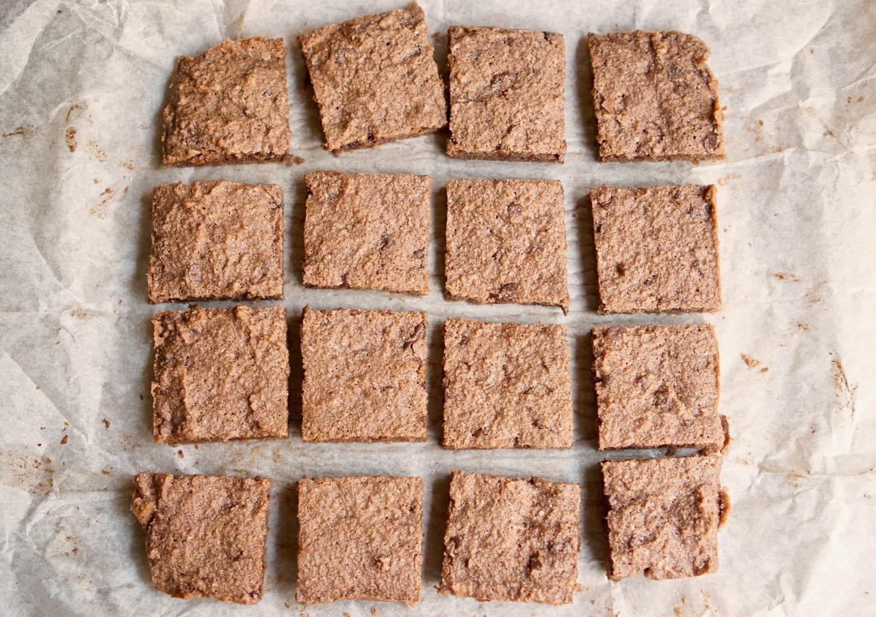 16 ריבועים על נייר אפייה. מתוך מתכון חיתוכיות שוקולד צ׳יפס ללא קמח בלוג גבישס.