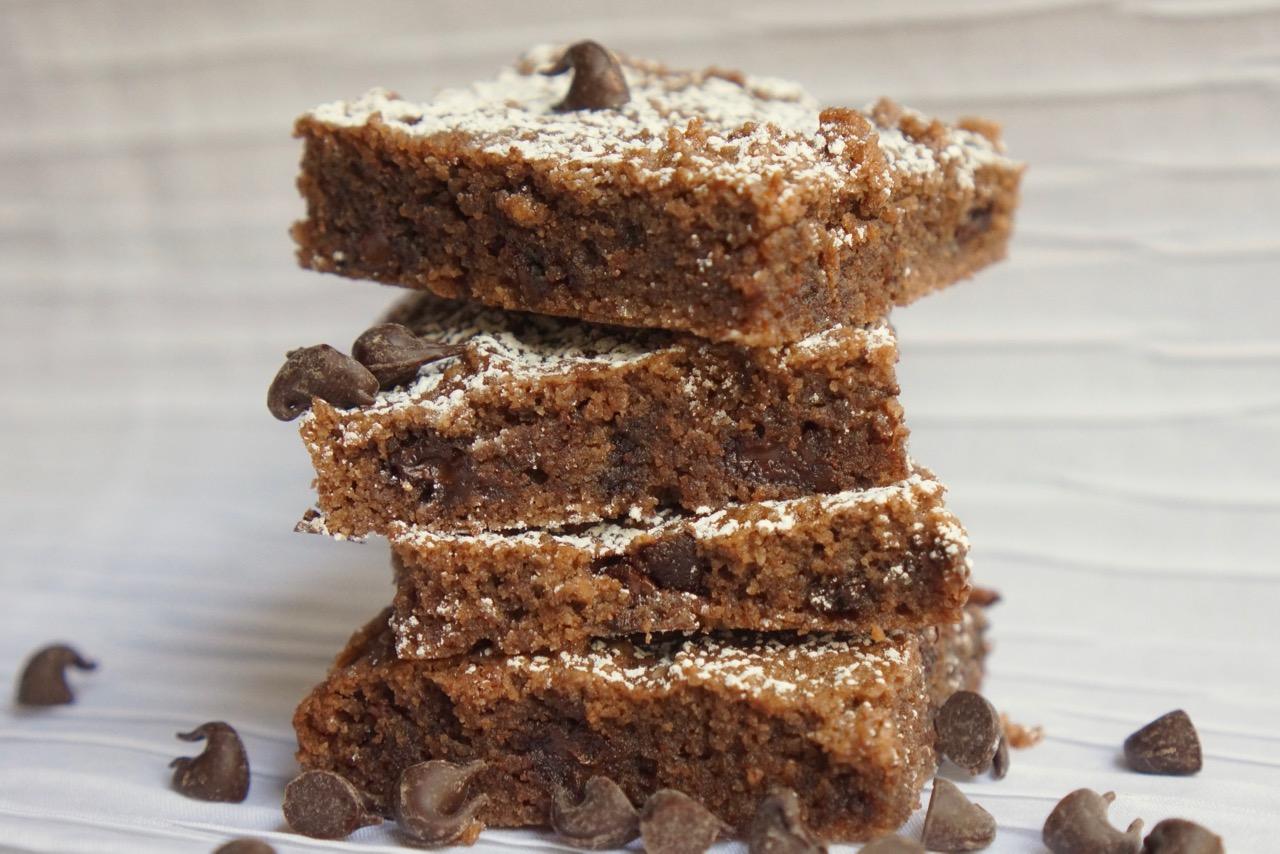 ריבועי שוקולד צ׳יפס מוכנים עם אבקת סוכר מונחים אחד על השני בערימה לגובה. מתוך מתכון חיתוכיות שוקולד צ׳יפס ללא קמח בלוג גבישס