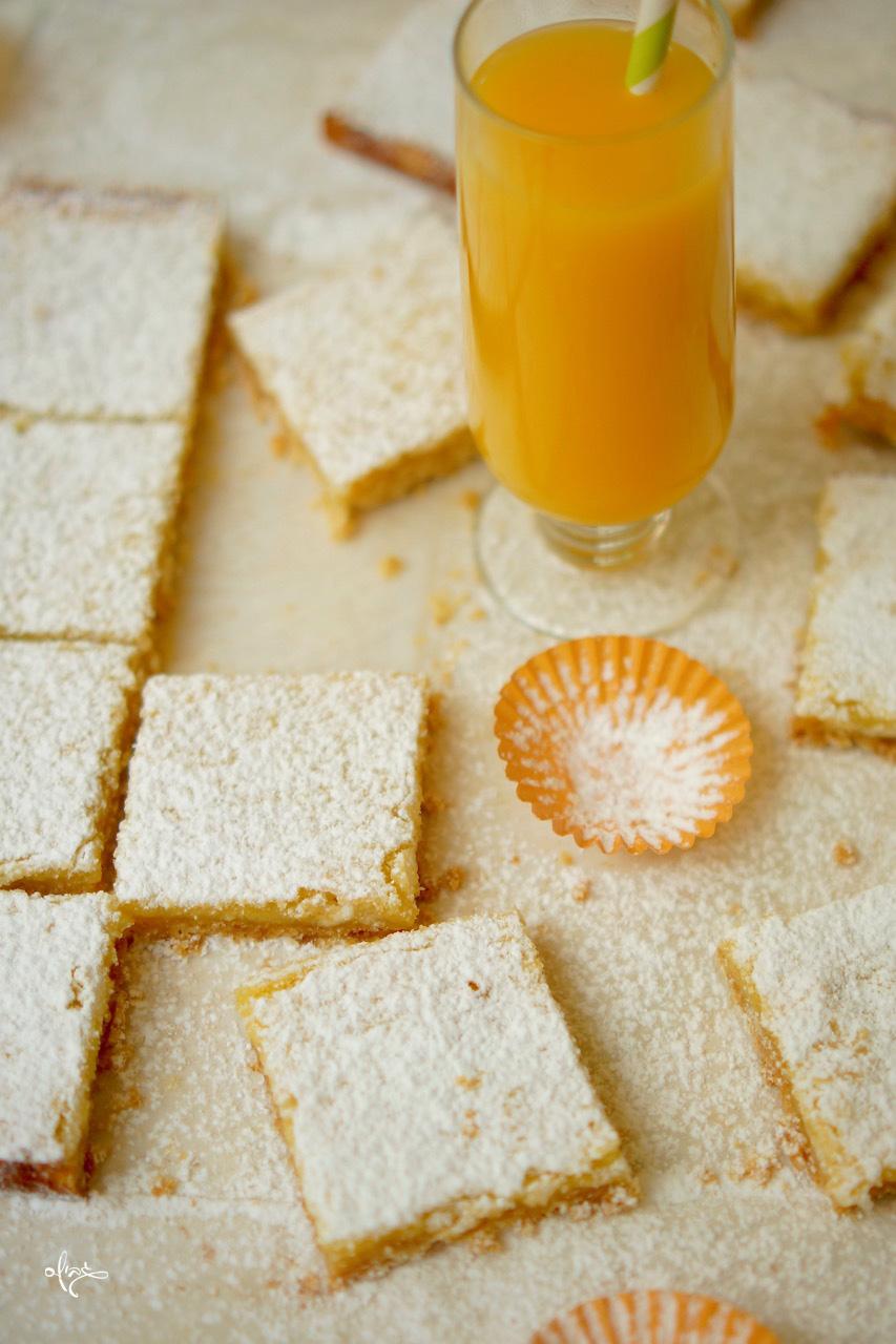 ריבועי תפוז חלומיים, עם כוס מיץ תפוזים ליד.