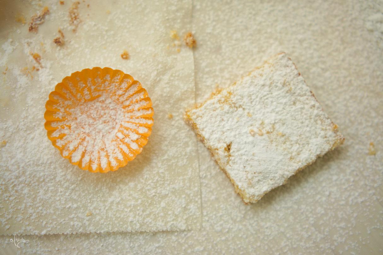 ריבועי תפוז חלומיים, ריבוע תפוז אחד על נייר אפייה עם אבקת סוכר מעל. מנג׳ט כתום קטן ליד.