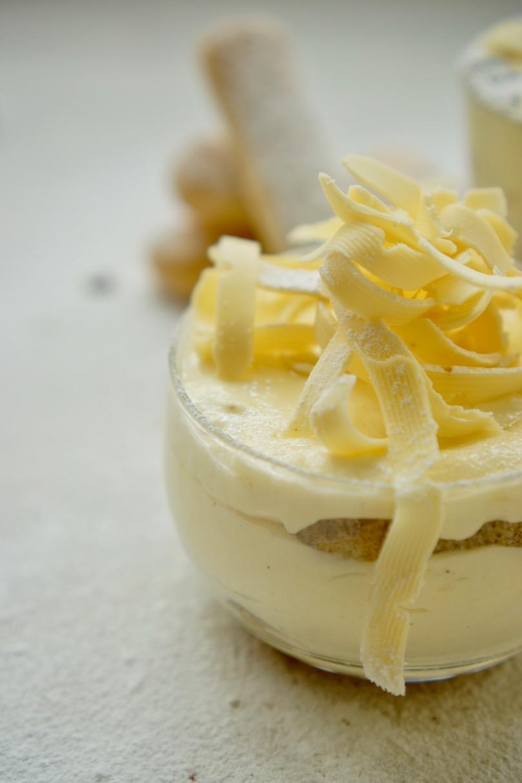 קינוח טירימיסו ושכבה גבוהה של תלתלי שוקולד לבן. אבקת סוכר מעל הכל.