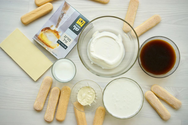המצרכים לטירמיסו. בישקוטי מפוזרים על שולחן, קופסת פודינג גרגירים של מאסטר שף, חפיסת שוקולד לבן, גבינת מסקרפונה בקערת זכוכית, שמנת מתוקה בקערית, חלב בקערית, שוקולד לבן מומס בקערית וקפה בקערית.