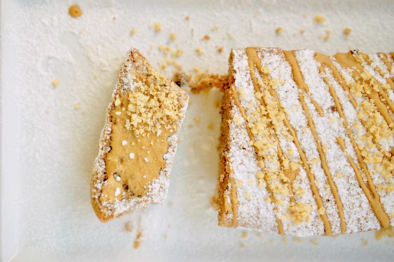עוגת אגוזים על משטח לבן. פרוסת עוגת אגוזים עם אבקת סוכר מעל וזיגוג קפה. מעל פזורים אגוזים קצוצים.