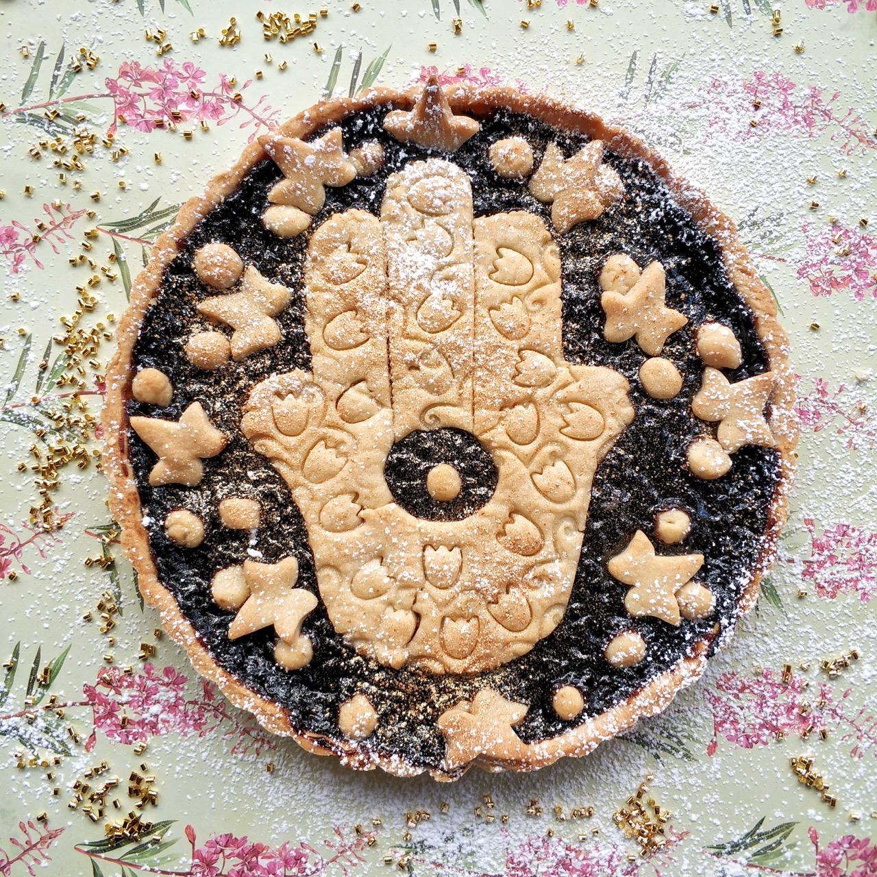 עוגת חמסה חמסה חמסה - עוגת בצק פריך וריבה עם צורת חמסה מעוטרת מבצק פריך מעל. מונחת על נייר פרחוני וחרוזים מזהב לקישוט.