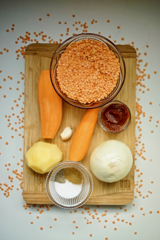 מרק עדשים כתומות של אחיות, בלוג האוכל של גבישס. רוב המצרכים למרק מונחים על קרש עץ. שמן זית, שום, בצל, גזר, רסק עגבניות, בטטה, תפוח אדמה, רסק עגבניות, עדשים כתומות.