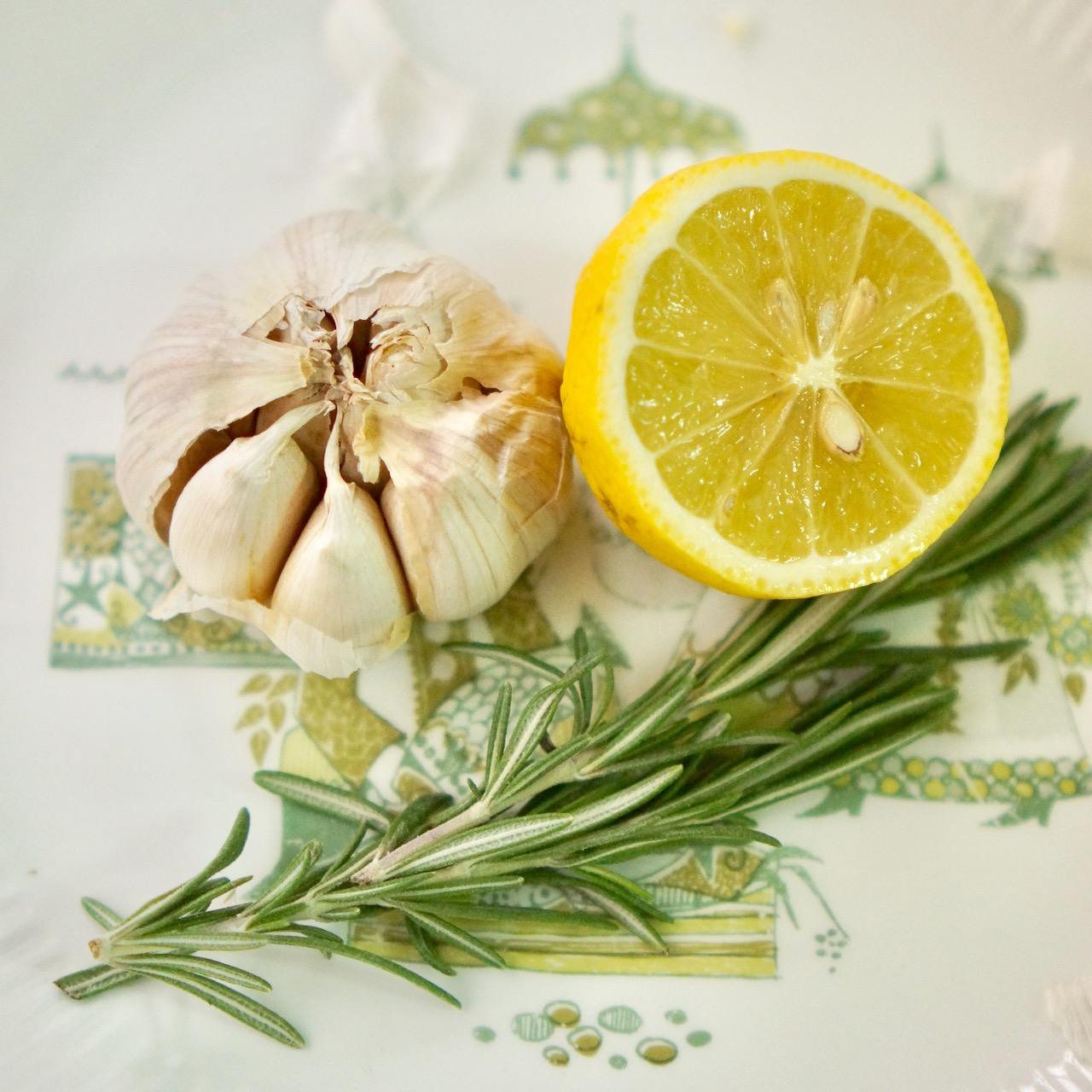 עוף צלוי עם לימון, שום ורוזמרין. ענף רוזמרין, ראש של שום ולימון מונחים על צלחת. גבישס, בלוג האוכל של גמירב גבישס.