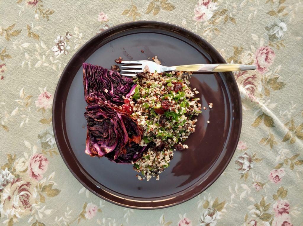 פרוסת כרוב סגול צלוי עם סלט קינואה מוגשים על צלחת סגולה, גבישס, בלוג האוכל של מירב גביש.