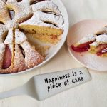 עוגת שזיפים בתבנית עגולה לבנה, צלחת ורודה עפ פרוס עוגה. עוגת שזיפים גבישס.
