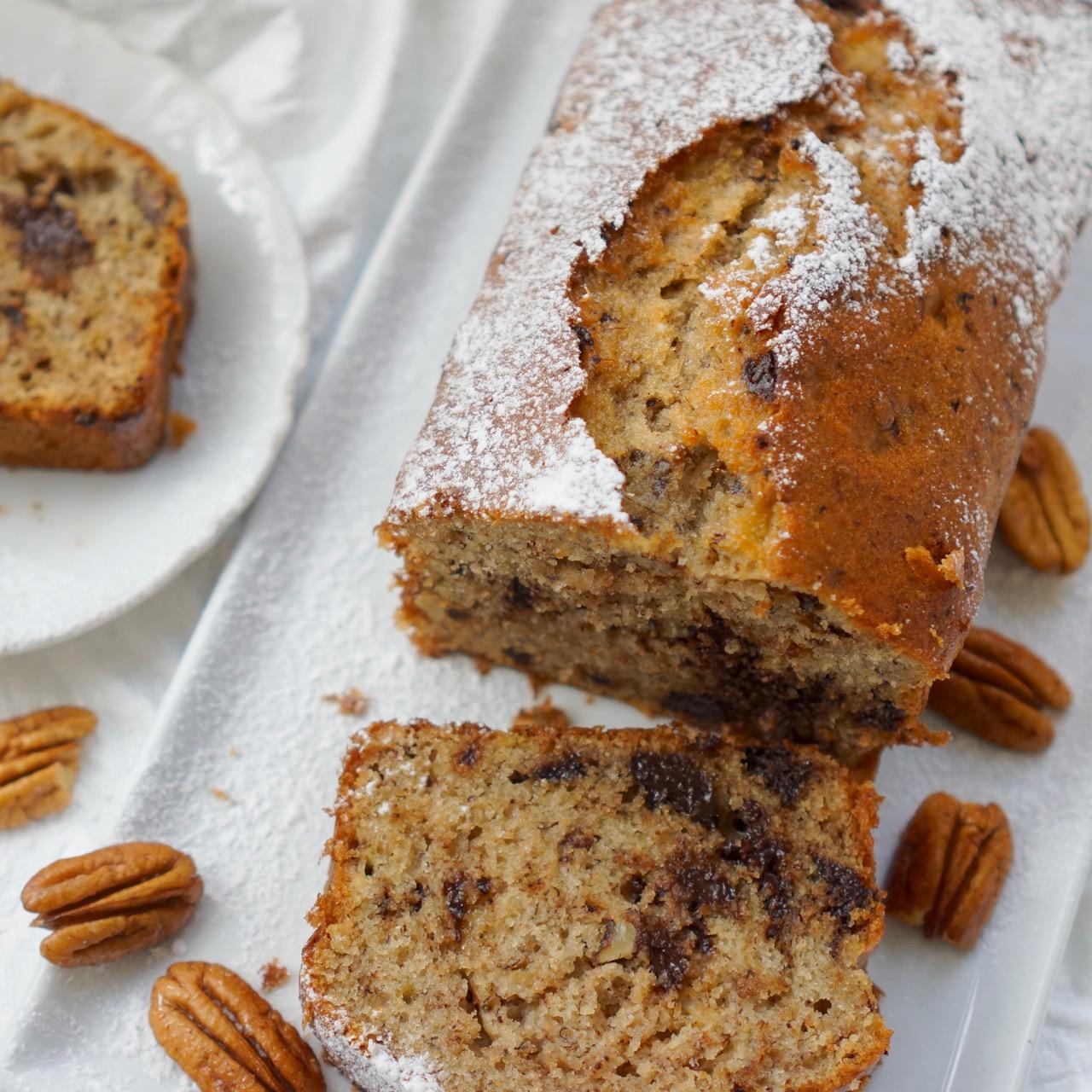 עוגת בננות ושוקולד מונחת על מגש מלבני ופקאנים מסביב