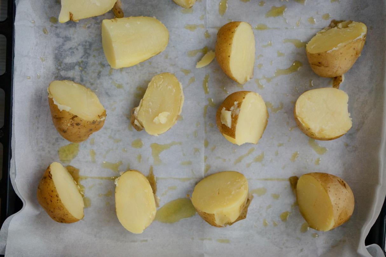 תפוחי אדמה מבושלים בקליפתם חצויים מונחים על תבנית משומנת